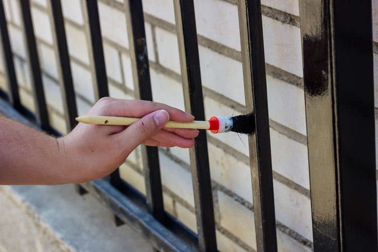Cropped image of hand painting gate