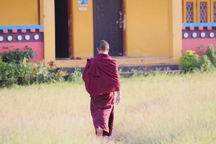 Rear view of buddhist monk walking on field