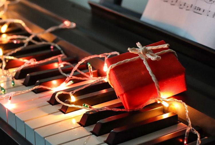 Illuminated christmas lights and gift box on piano