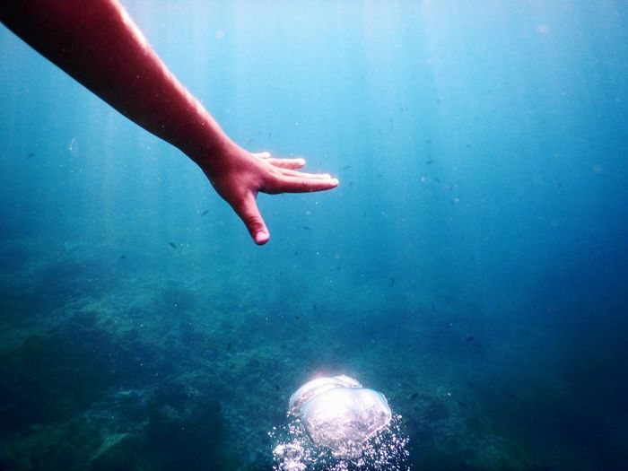 Cropped Hand Of Man Reaching For Bubbles Undersea