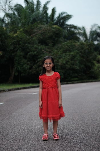 Looking At Camera Portrait Road Full Length One Person Standing Tree Child Girls Front View Real People Childhood Females Women Plant Transportation Casual Clothing Red Clothing Innocence Hairstyle