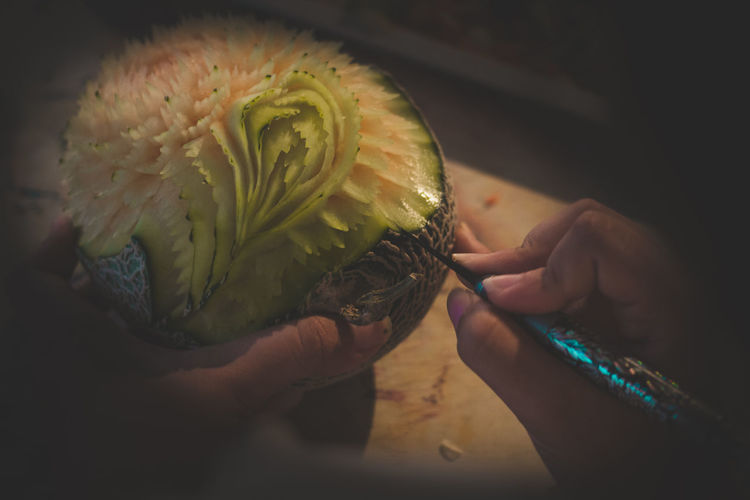 Cropped Image Of Woman Making Artwork On Cantaloupe