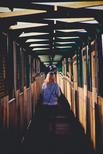 Rear view of woman crossing footbridge