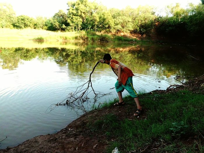 He was checking water's depth with tree bushes Adventure Club Nature Forest Beauty In Nature Summer Boy In Nature Greenery And Water Outdoors Checking Depth Discover  Near The Water Discovering Boy Adventure Jungle Boy In Action