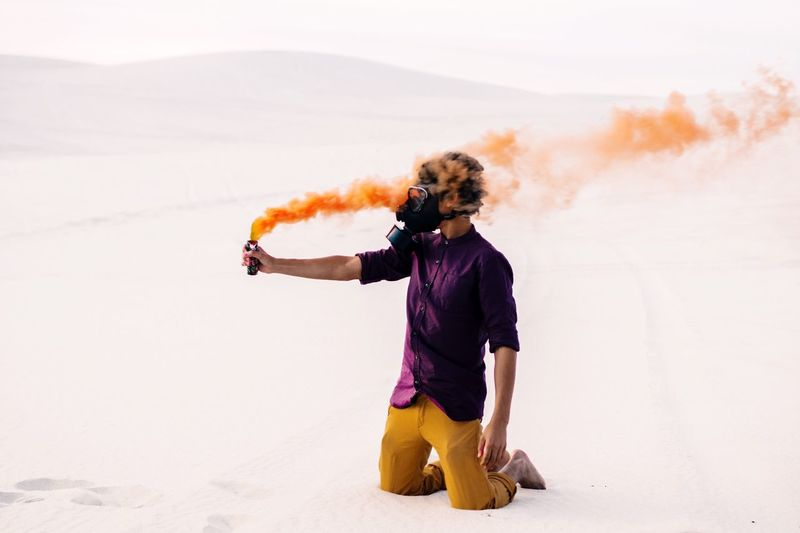 Man in gas mask holding distress flare on desert