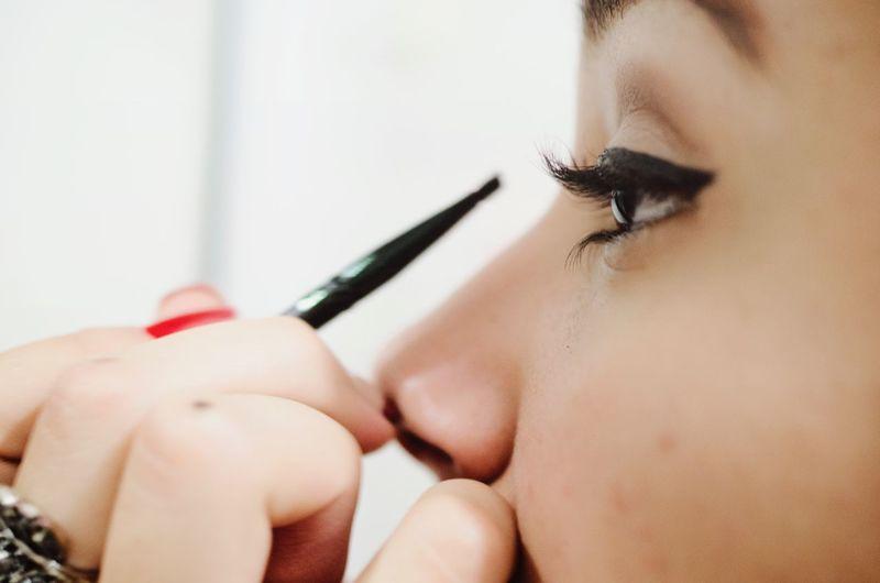 Cropped image of woman applying eyeliner