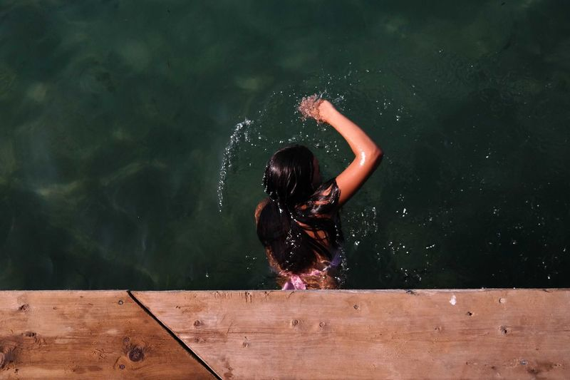 Directly above view of woman swimming in lake