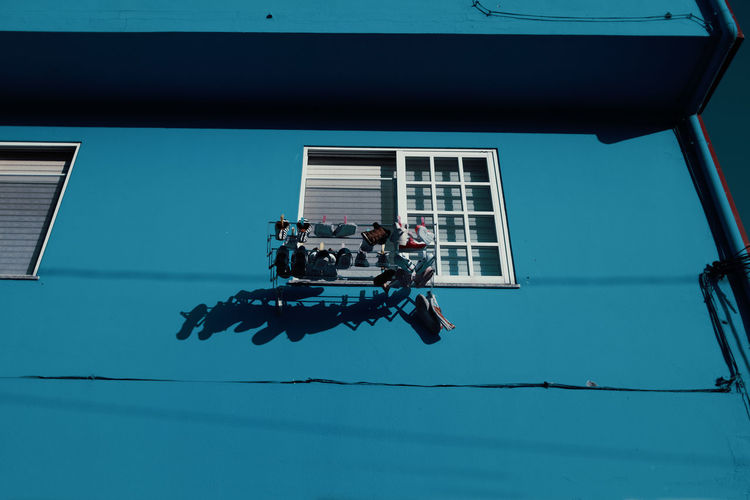 Low angle view of shoes drying by window of house during sunny day