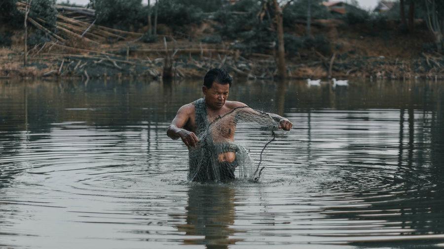 Full length of shirtless man in lake