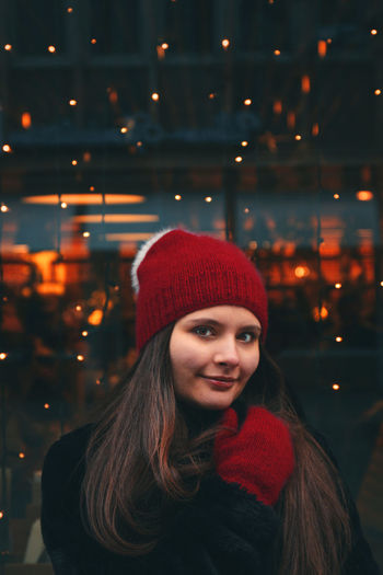 Portrait of smiling woman in illuminated park during winter at night