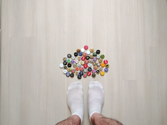 Low section of man wearing socks while standing by various bottle caps on hardwood floor