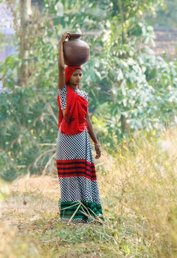 A lady carrying water. Life goes on in a village with a lady carrying water pot on her head probably drawn from a nearby well Bare Neccesities Lady Carrying Water Lifestyles Outdoors People Pot Of Water Traditional Traditional Clothing Tranquil Scene Tranquility Travel Village Life Water