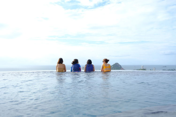 Rear view of friends relaxing in infinity pool