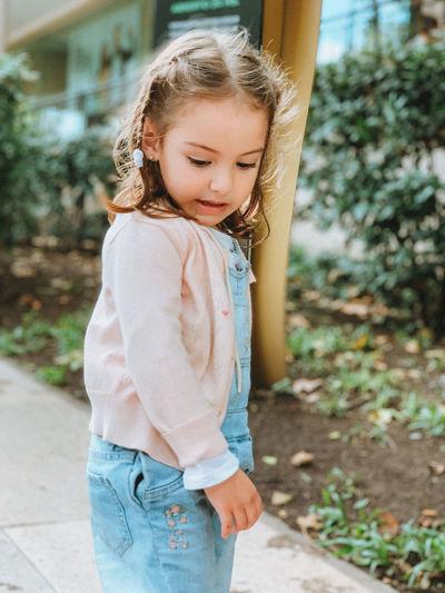 Full length of smiling girl standing outdoors