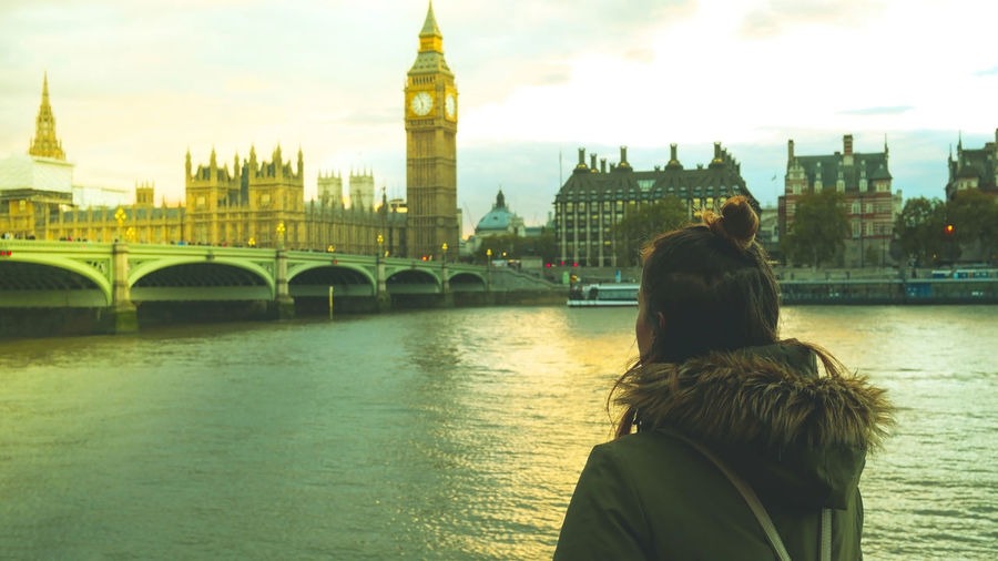 Rear view of woman standing against big ben in city