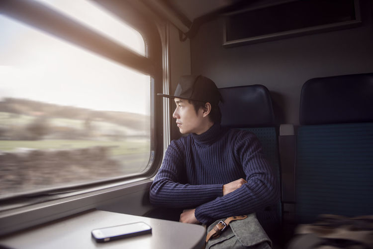 Young man looking through window while traveling in train