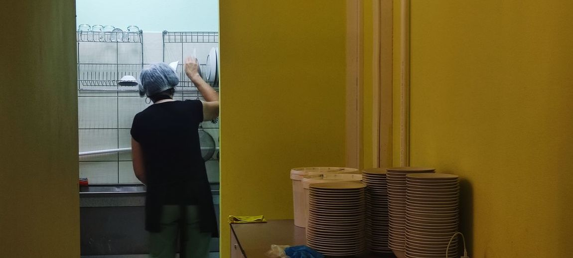 Rear view of man working on window