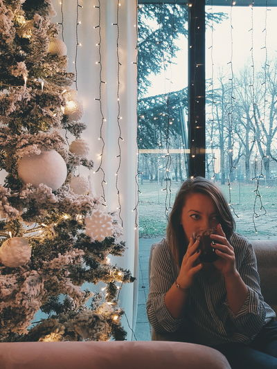 Woman Drinking Coffee While Sitting On Sofa At Home During Christmas