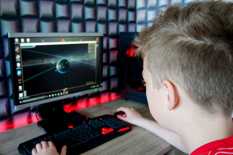 Close-up of boy playing computer game