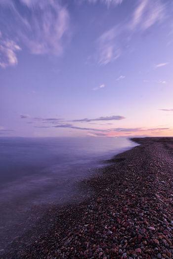 Rocky beach coast, sunset, small stones, long exposure, silk effect, infinite horizon, magenta