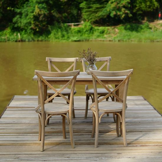 Empty chairs with table arranged on pier over lake