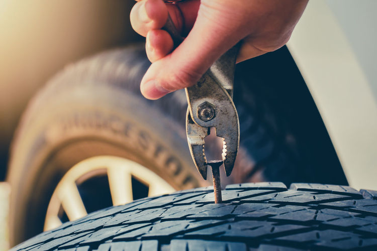 Cropped hand of person removing nail from tire