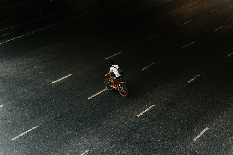 High angle view of a biker crossing a big inner city street Transportation Motion Mode Of Transportation Riding One Person Ride Full Length Sign Speed Road Sport City Bicycle Land Vehicle Motorcycle High Angle View Day Real People Stunt Outdoors Bike Biking Highway Street Transportation