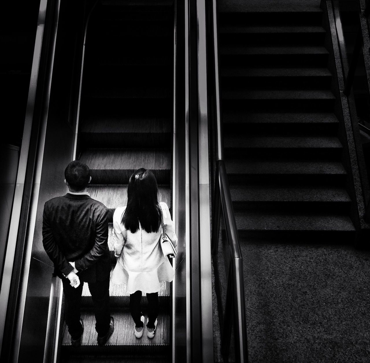 High Angle View Of Man And Woman On Escalator