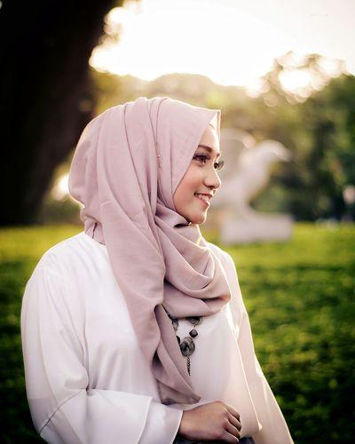 Smiling beautiful woman wearing hijab looking away at park