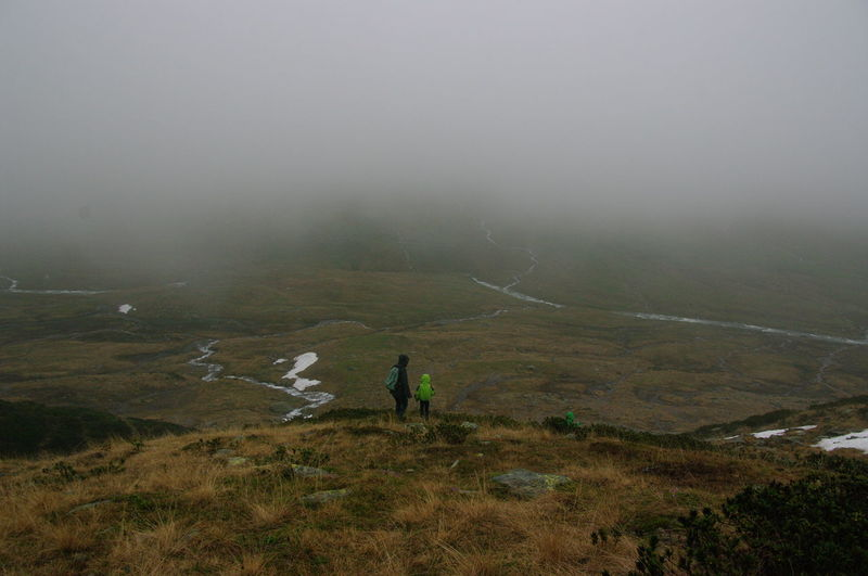 Adult Beauty In Nature Day Fog Full Length Grass Landscape Leisure Activity Lifestyles Men Mountain Nature Outdoors People Real People Scenics Sky Standing Two People Lost In The Landscape