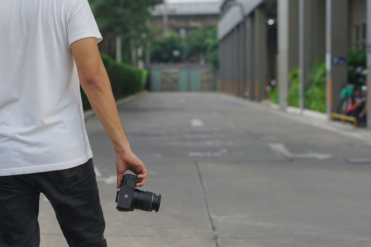 Midsection of man photographing on street