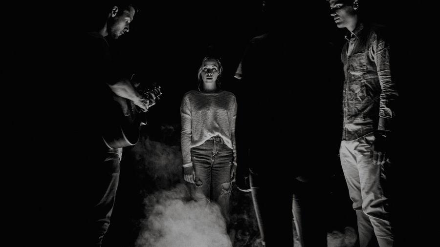 Digital composite image of people standing in illuminated dark