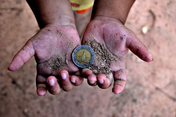Cropped dirty hands of child holding coin outdoors