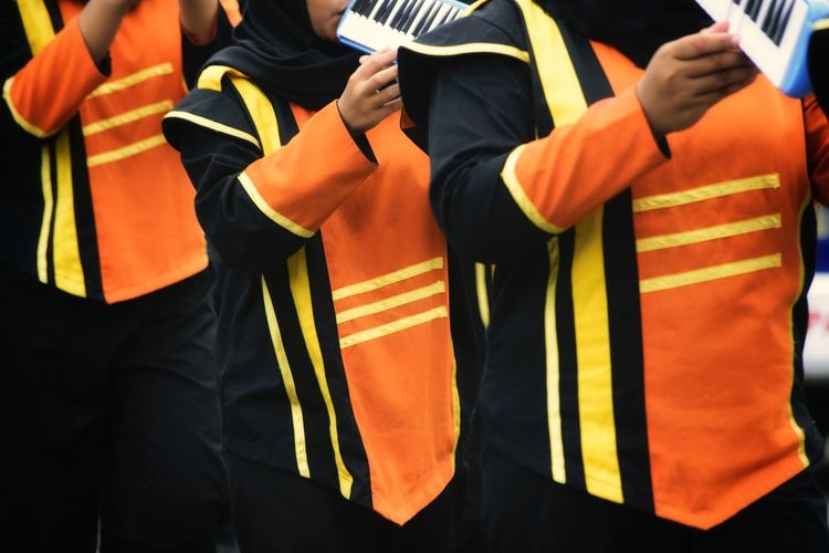 Midsection of musicians wearing uniform