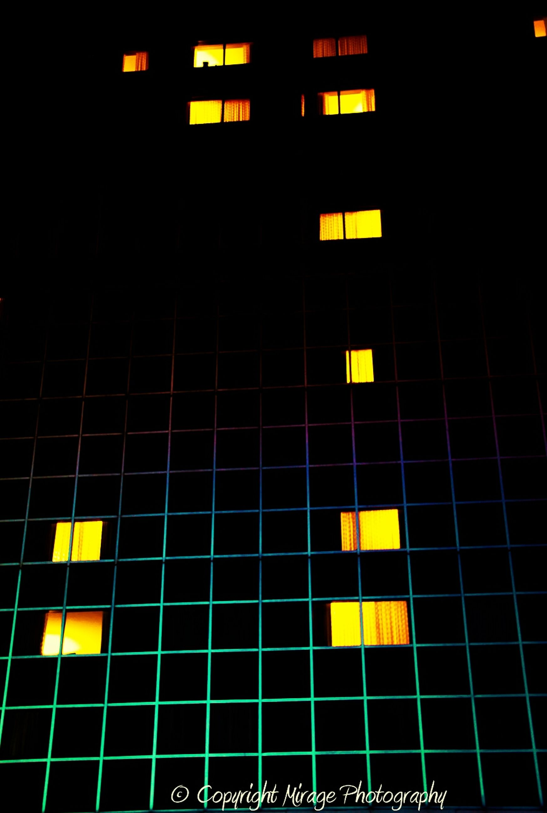 illuminated, architecture, built structure, yellow, building exterior, full frame, night, backgrounds, low angle view, pattern, window, building, city, modern, lighting equipment, no people, outdoors, repetition, geometric shape, glass - material