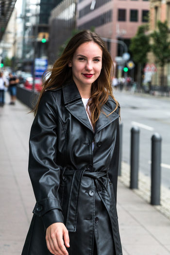 Portrait of young woman wearing a trench coat in city One Person City Looking At Camera Long Hair Brunette Outdoors Trench Coat Three Quarter Length Portrait Young Adult Beauty Young Woman Focus On Foreground Caucasian Attractive Fashion Beautiful Woman Front View Real People