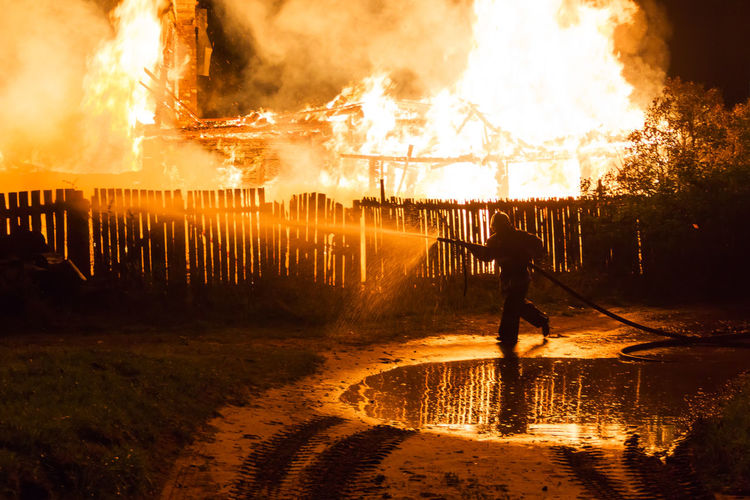 Firefighter Spraying Water From Hose On Burning House At Night