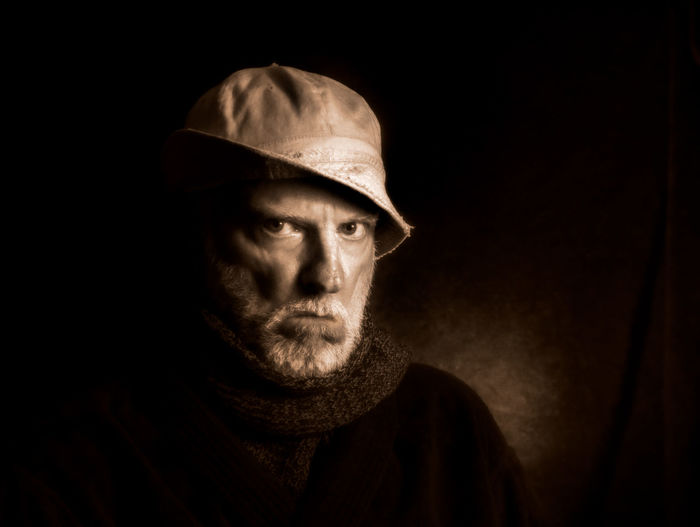 A portrait of a very serious man Black Background Fisherman Gangster Looking At Camera Mature Adult Mature Men Night One Man Only Painter Portrait Real People RESOLUTE Serious