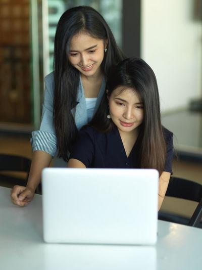 Smiling businesswomen using laptop at office