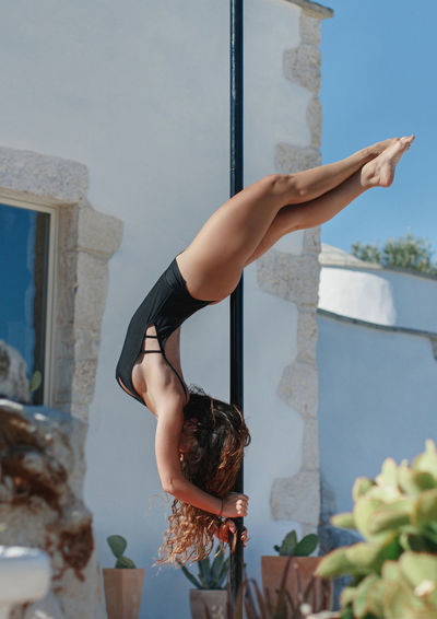 Full length of woman exercising by pole outdoors