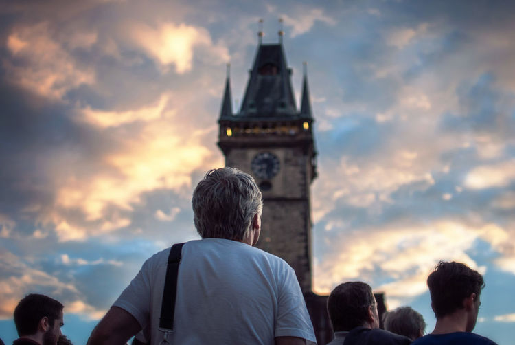 Rear view of people by astronomical clock tower against cloudy sky during sunset
