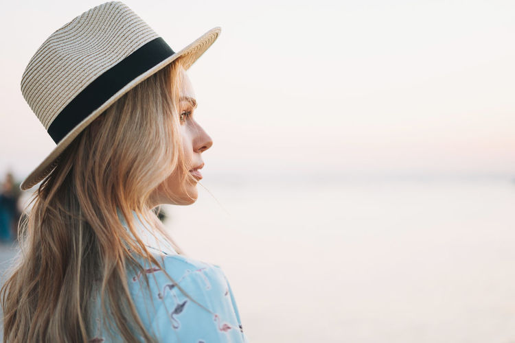Portrait of beautiful blonde young woman in blue dress and straw hat on pier on sunset