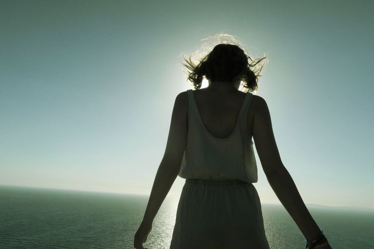 Silhouette Of Woman Standing Against Sun