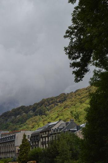 Houses on mountain against cloudy sky
