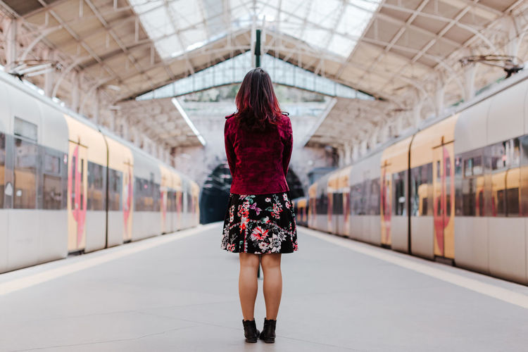 Rear view of woman standing on train at railroad station