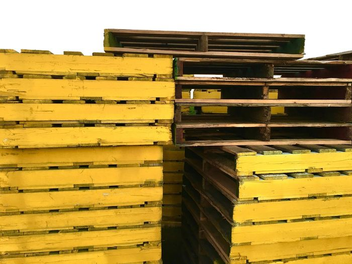 Close-Up Of Yellow Wooden Palettes In Warehouse