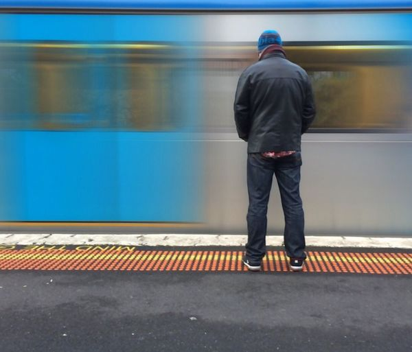 Rear view of man standing against speeding train at station