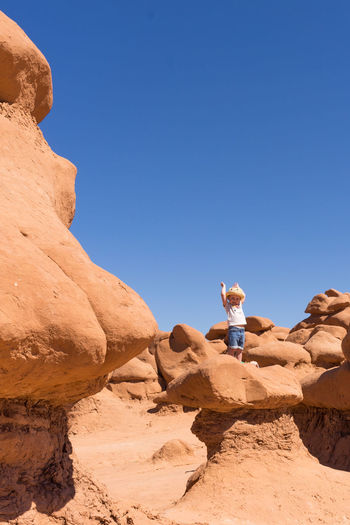 Rear view of young woman standing on rock formation against clear blue sky