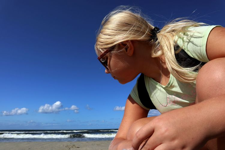 Girl crouching at beach against blue sky