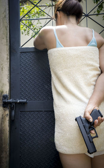 Rear View Of Woman Holding Handgun Behind Her Back By Gate